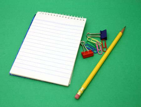 yellow pen and paper clips besides an open notebook on a green surface Stock Photo