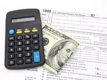 calculator and dollar bills over 1040 tax form photo