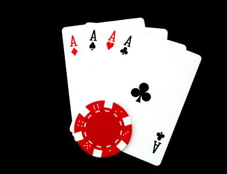 four aces and a gambling chip isolated on black