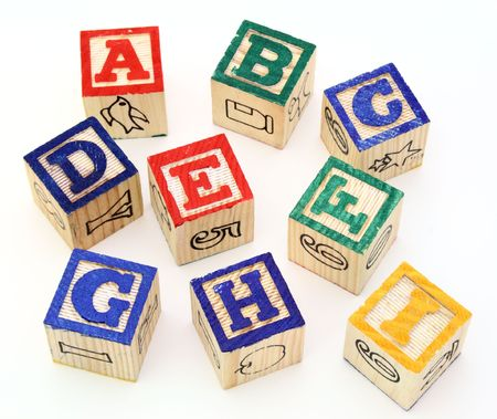 several alphabet blocks scattered on a white surface