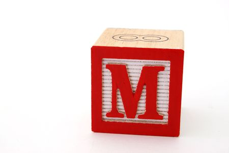 letter m in an alphabet wood block on a white surface
