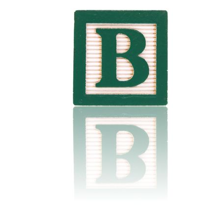 letter b in an alphabet wood block on a reflective surface