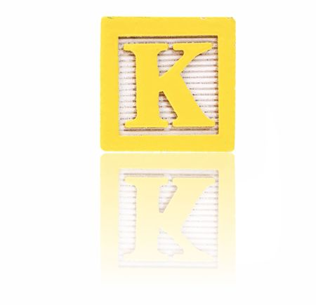 letter k: letter k in an alphabet wood block on a reflective surface