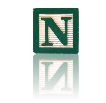 letter n in an alphabet wood block on a reflective surface