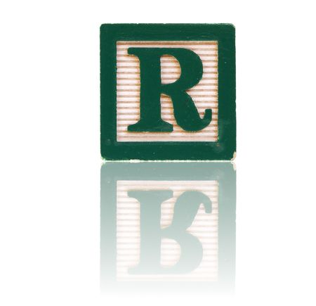 letter r in an alphabet wood block on a reflective surface