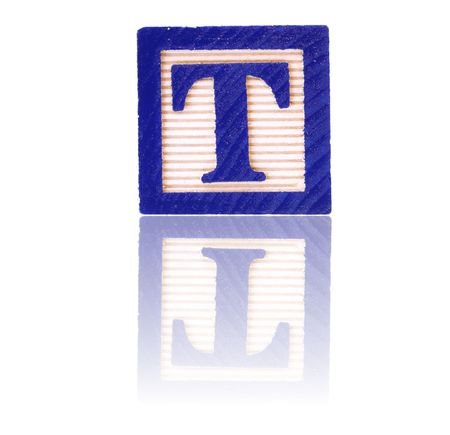 letter t in an alphabet wood block on a reflective surface