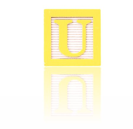 letter u in an alphabet wood block on a reflective surface