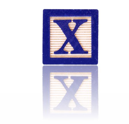 letter x in an alphabet wood block on a reflective surface