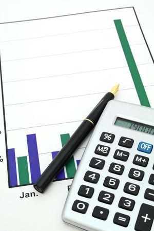 fountain pen and silver calculator over a graph Stock Photo