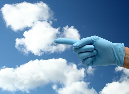 hand in blue gloves pointing under a blue sky