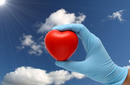 heart under: hand in latex blue gloves holding a toy heart under a blue sky