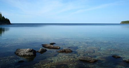 clear waters: rocks on waters of a lake under a clear sky Stock Photo