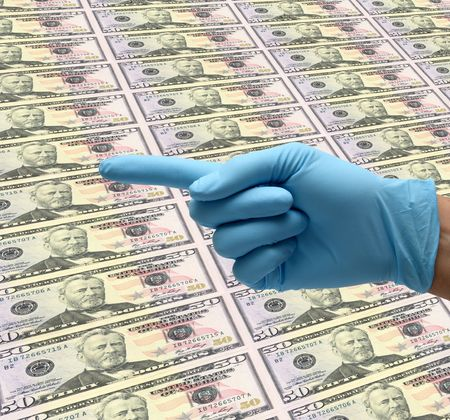 hand in blue gloves pointing over a background of dollar bills photo
