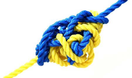 yellow and blue ropes tied by a complicated knot isolated on white