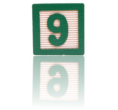 number nine in an alphabet wood block on a reflective surface Stock Photo - 6543976