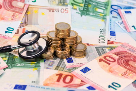 Euro banknotes, coins and stethoscope