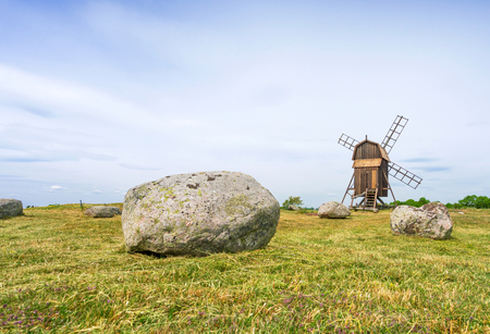 windy energy: Old wooden windmills and stones on the island Oland, Sweden
