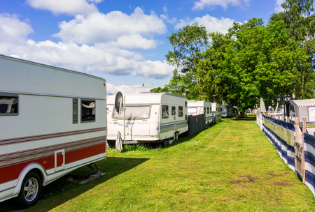 View of a camping, camp sites on the Baltic Sea, Sweden. Cars and caravans, wooden porch. Forest in the background.