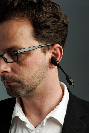 A man, about 40 years, with a USB cable in his ear