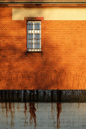 The outside view of an old and abandoned jail in Berlin during sunset Stock Photo