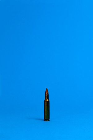A single bullet is standing on a blue ground