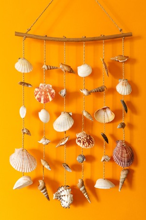 A wind chime with shells on a yellow background on a stick Stock Photo