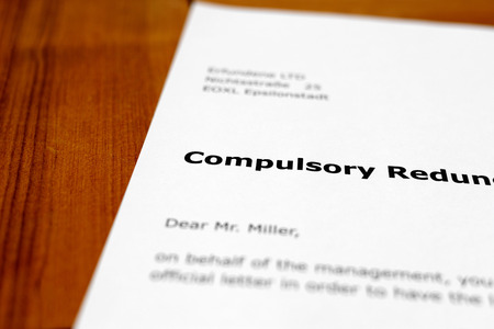 compulsory: A letter on a wooden table - compulsory redundancy