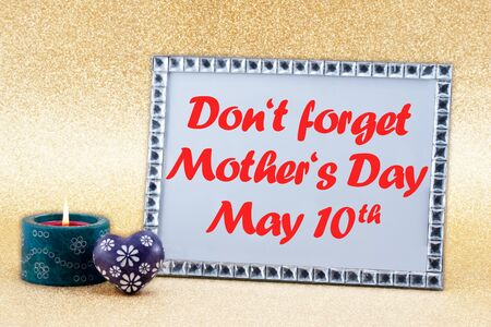 A burning candle, heart and a picture frame with the text DO NOT FORGET MOTHER'S DAY