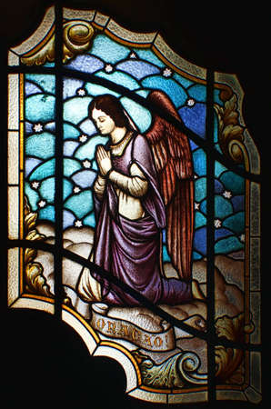 Stained glass of an angel, in the main door or Valongo Church, in Santos, Brazil, asking for you to pray, with the text praying written in Portuguese below the angel. photo