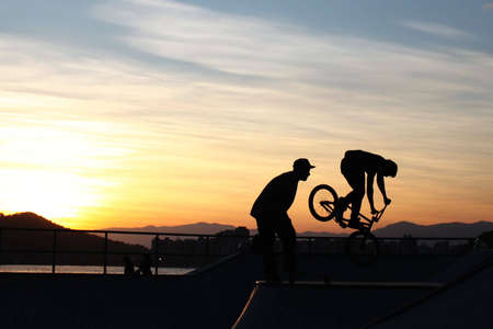 bmx bike: BMX Bike flying off the track with the sea, horizon and sunset in the background. Also shows the perfect silhouette of another guy looking amazed to the BMX.