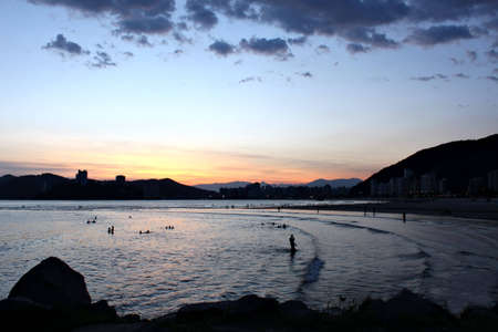 Beach of Itarare in Sao Vicente, Brazil. View from the rocks of Emissario Submarino in Santos, Brazil, to Sao Vicente. Showing people silhouettes playing in the water. Banco de Imagens