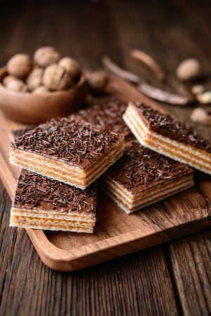 Homemade sweet wafer filled with walnut toffee filling and topped with chocolate frosting on wooden background