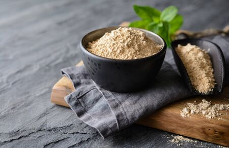 Dietary supplement, Maca root powder in a bowl and scoop on stone background with copy space Stock Photo