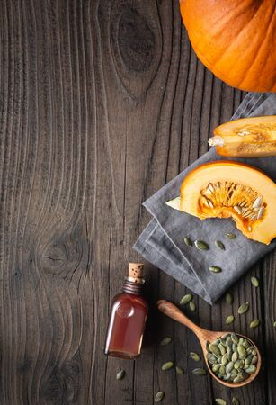 Cold pressed Pumpkin seed oil in a glass bottle, decorated with peeled seeds on wooden table with copy space