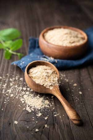 Dietary supplement, unfortified nutritional yeast flakes in a wooden bowl and scoop on wooden table Banque d'images