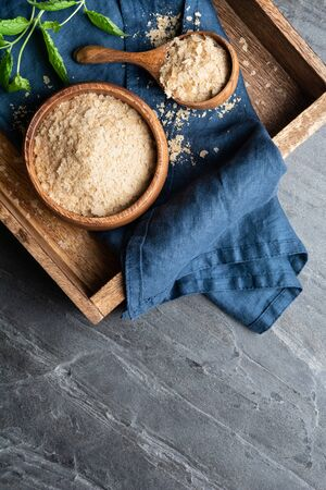 Dietary supplement, unfortified nutritional yeast flakes in a wooden bowl and scoop on stone backdrop with copy space