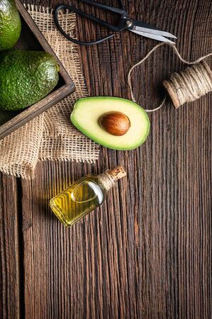 Healthy avocado oil in a glass bottle, decorated with sliced avocado on wooden background with copy space