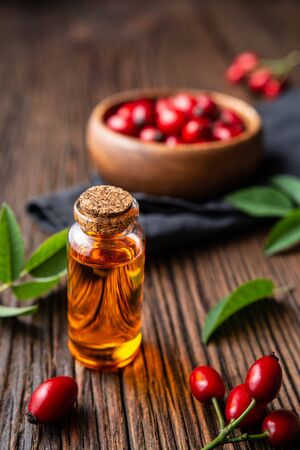 Pure rosehip seed oil in a glass bottle, remedy for skin and hair on rustic wooden background