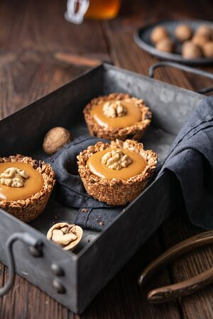 Sweet snack, homemade cinnamon granola cups with raisins and sunflower seeds, filled with toffee, topped with walnut