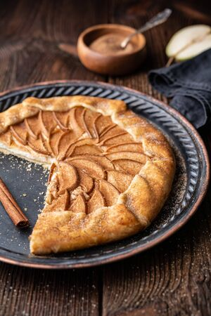 Juicy pear Galette with cream cheese filling, sprinkled with cinnamon sugar on rustic wooden background