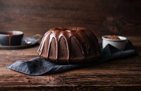Delicious dessert, dark chocolate bundt cake topped with ganache glaze on rustic wooden background Imagens