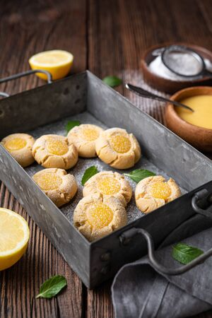 Delicious sweet snack, lemon crud thumbprint cookies sprinkled with powdered sugar on rustic wooden background Standard-Bild