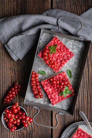 Sweet red currant dessert filled with cream cheese, decorated with fresh berries on wooden background