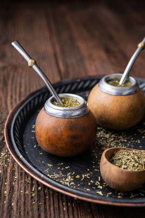 Healthy infused drink, classic Yerba Mate tea in a gourd with bombilla on wooden background