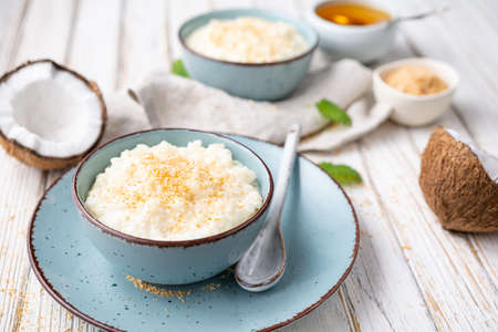 Sweet and creamy coconut rice pudding with honey, topped with grated and toasted coconut in a ceramic bowl
