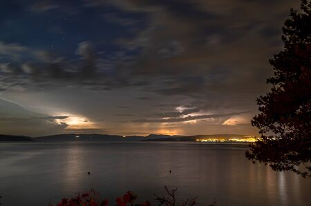 Thunderstorm by night on a see in Croatia, on the opposite side a illumined big city Stock fotó
