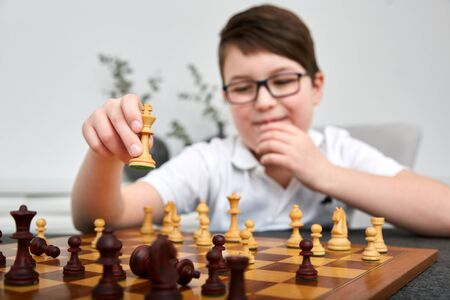 Small intelligent boy play chess and looks very clever and strategic, boy makes a move