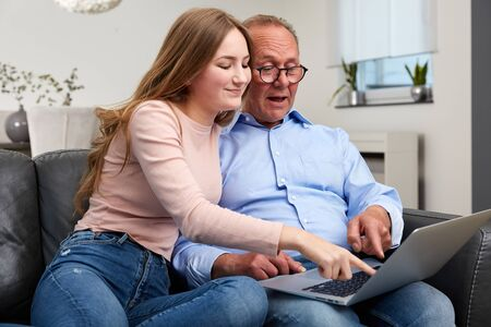 Grandpa sits with the granddaughter on the couch with the laptop and together they have great fun