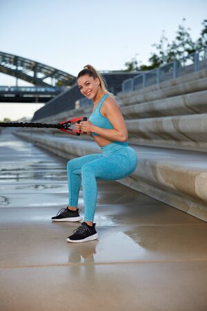 Early in the morning, after sunrise, in the city by the river, a young attractive woman makes fitness workouts on the promenade, outdoor and functional strength training with an elastic band