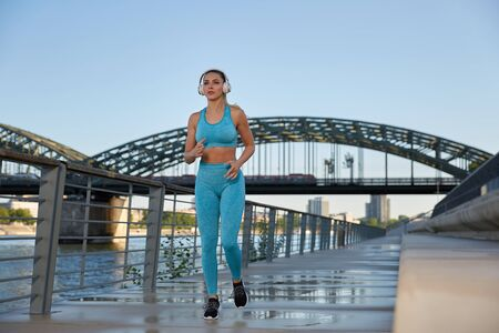 Early in the morning, after sunrise, in the city by the river, a young attractive woman goes jogging on the promenade and listens to music through headphones